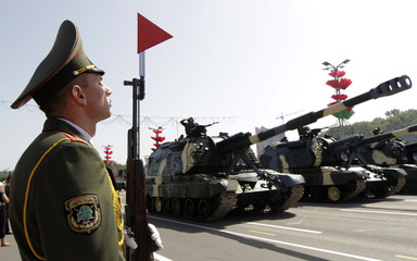 Serviceman takes part in a military parade, as Belarussian army vehicles move in the background, during celebrations marking Independence Day in Minsk
