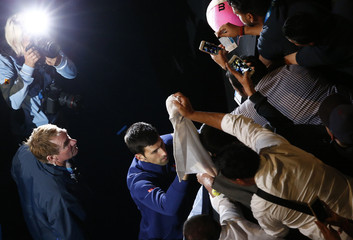 Serbia's Djokovic signs autographs after winning his final match against Britain's Murray at the Australian Open tennis tournament at Melbourne Park