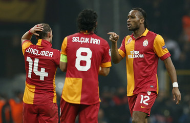 Galatasaray's Drogba celebrates with his team mates Sneijder and Inan after scoring a goal against Real Madrid during their Champions League quarter-final second leg soccer match in Istanbul