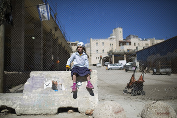 A Jewish settler girl is dressed in a costume during a parade marking Purim in Hebron
