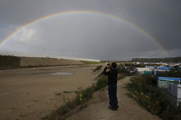 "An Afghan migrant youth uses a mobile phone to photograph a rainbow that appears over the makeshift camp called the ""Jungle"" in Calais"