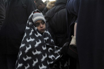 A girl is covered with a blanket as migrants wait to cross the Greek-Macedonian borders near the village of Idomeni