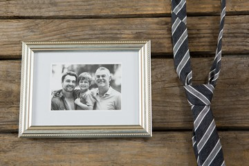 Overhead view of picture frame by necktie on table