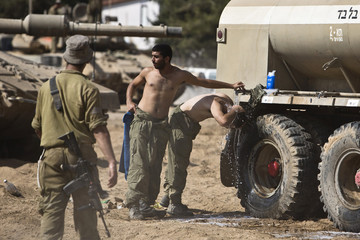 Israeli soldiers wash themselves at a staging area near border with the Gaza Strip