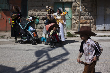Jewish settlers and their children dressed in costumes take part in a parade for the Jewish holiday of Purim in Hebron