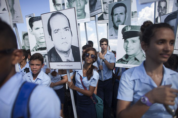 Students hold photographs of victims from events such as the Bay of Pigs invasion and the bombing of a Cuban plane during a march in Havana