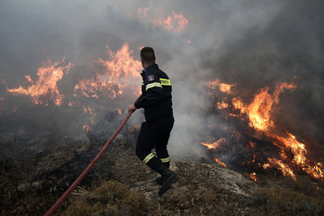 A firefighter tries to extinguish a forest fire near Keratea