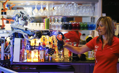 """Humanoid robot bartender """"Carl"""" pours a spirit into the cocktail shaker of a bartender to prepare a drink for a guest at the Robots Bar and Lounge in Illmenau"""