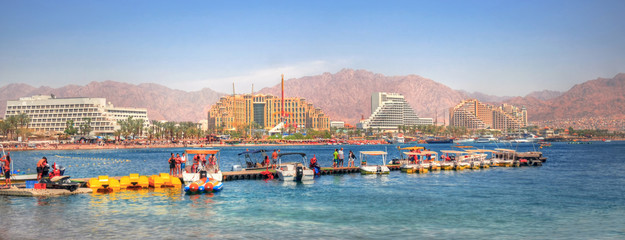 People and boats in a pier in Eilat in the background of the new harbor of Eilat with its beautiful resorts, Israel - panoramic image