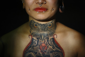 """Tattoo of an owl is pictured on the neck of Jharana Gurung, the first woman from Nepal to perform a body suspension, as she poses for a picture backstage during the """"Nepal Inked - A Tattoo and Lifestyle Convention"""" in Kathmandu"""