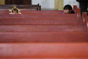 A girls sits with a dressed-up doll representing baby Jesus, in a pew before a mass 40 days after the birth of Jesus in Xochimilco