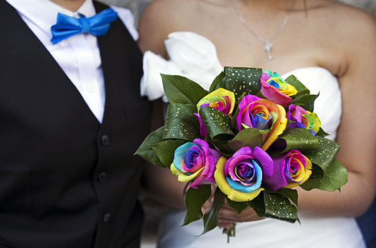 """Lee stands next to her partner Chang Ho holding a rainbow-coloured bouquet of flowers, before they take part in """"Celebration of Love"""" at Casa Loma in Toronto"""