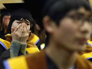 A high school graduate who escaped from North Korea weeps during a graduation ceremony at Hangyeore Middle and High School, which was built to educate North Korean teenage defectors, in Anseong