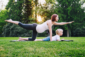 Pregnant woman doing yoga with son on nature outdoors.
