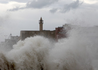 A wave crashes into the waterfront at Sidon port-city in south Lebanon during a storm