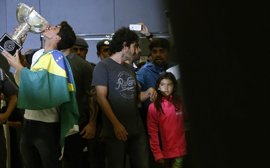 Gabriel Medina kisses the ASP World Championship Tour title trophy next to his sister Sophia as he arrives at Guarulhos airport in Sao Paulo