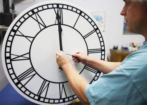 Scott Gow assembles a clock dial at the Electric Time Company in Medfield