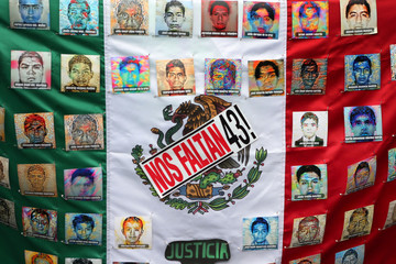 A Mexican flag and some pictures of the 43 missing students is seen in a march to demand justice for the 43 missing students of Ayotzinapa College Raul Isidro Burgos to mark the two-year anniversary of their disappearance in Guerrero, Mexico City