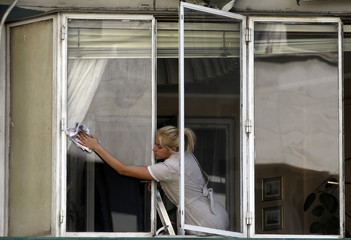 A maid cleans windows in an apartment blick in Madrid