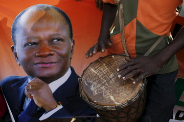 A supporter of Ivory Coast's President Alassane Ouattara plays a drum next to a portrait of Quattara while waiting for the president's arrival  in the city of Kani