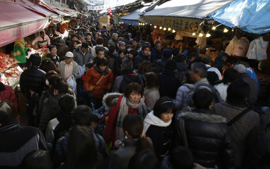 People walk at a street as they do their last-minute New Year's shopping in the Ameyoko shopping district in Tokyo