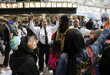 Security guards eject protesters as they rally in support of higher pay for low-wage earners at a McDonald's restaurant in Washington