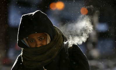 A woman walks in frigid cold temperatures though downtown Chicago