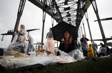 People picnic and have breakfast on the main deck of the Sydney Harbour Bridge as it rains during the Breakfast on the Bridge event in central Sydney