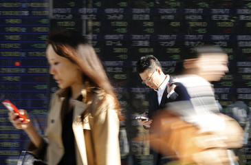 Pedestrians using their mobile phone walk past an electronic board displaying various stock prices outside a brokerage in Tokyo