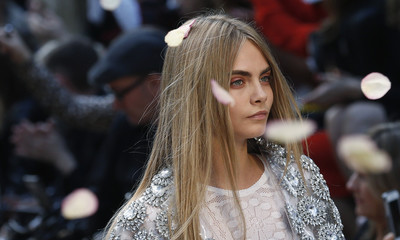 Model Delevingne presents creation from the Burberry Prorsum Spring/Summer 2014 collection during London Fashion Week