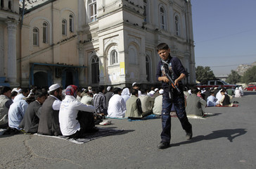 A boy plays with a toy gun as people take part in morning prayers outside the Shah-e Doh Shamshira mosque on the first day of the Muslim holiday of Eid-al-Fitr in Kabul