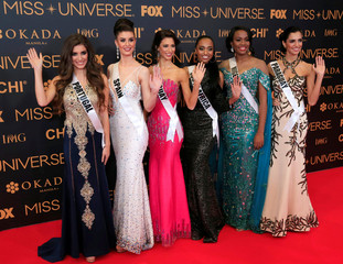 Miss Universe candidates gestures for a picture during a red carpet inside a SMX convention in metro Manila