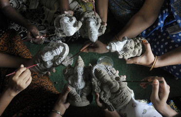Students apply natural colours on idols of Hindu elephant god Ganesh in Hyderabad