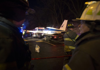 A single engine plane is loaded onto a flat bed truck after landing on Major Deegan Expressway in the Bronx borough of New York