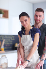 Young couple prepared cake standing in the kitchen