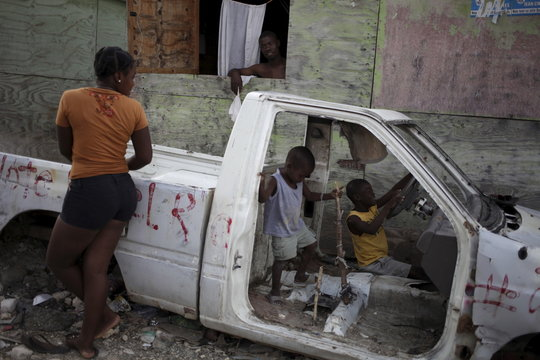 A woman talks to a man as two children play inside a wrecked car at a camp for displaced people in Port-au-Prince, Haiti