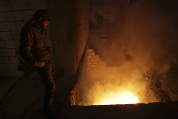 A Free Syrian Army fighter inspects a fire that activists said was started by an incendiary bullet fired by forces loyal to Syria's president Assad in Deir al-Zor