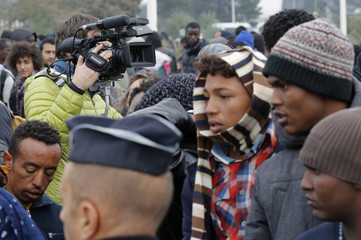 """A TV cameraman films as migrants with their belongings queue at the start of their evacuation and transfer to reception centers in France, and the dismantlement of the camp called the """"Jungle"""" in Calais"""