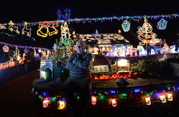 Eric Marshall poses for a photograph after switching on his Christmas lights for the first time this year on his house in Bagby, northern England
