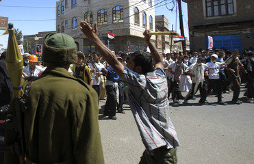 Defected army soldier stands guard as an anti-government protester shouts to fellow protesters to proceed as they march in Sanaa
