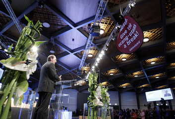 Nestle Chief Executive Bulcke (back) gives his speech while a Greenpeace activist holds a placard on the ceiling against the destruction of the rainforest to produce palm oil during the firm's annual general meeting in Lausanne