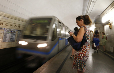 Commuters stand on a platform as a metro train arrives at a station in Moscow