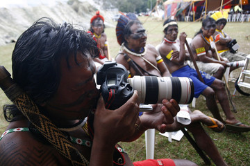 A member of the indigenous activist group APIB tries a photojournalist's camera as they gather in the Esplanade of Ministries for the annual Free Land Encampment in Brasilia