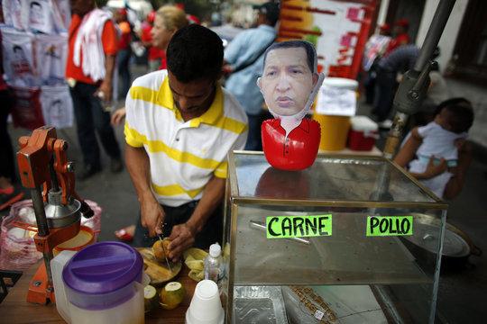 A man prepares orange juice next to a puppet depicting Venezuela's President Hugo Chavez outside the military hospital after his surprise return to Caracas