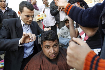 An anti-government protester has a haircut during demonstrations inside Tahrir Square in Cairo