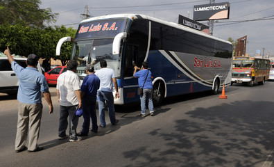 """Former bus drivers ask people for money to help support their protest in which three of their companions """"self-crucified"""" themselves in protest over their dismissal from work, in Asuncion"""