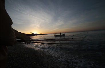 A fisherman drags his net on a beach during the traditional Poutine fishing in Cagnes-Sur-Mer