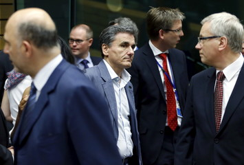 Greek Finance Minister Tsakalotos walks past Lithuanian counterpart Sadzius and European Economic and Financial Affairs Commissioner Moscovici during an euro zone finance ministers meeting in Brussels