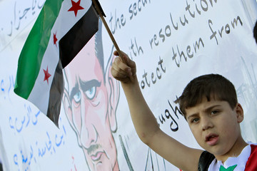 A Syrian boy living in Jordan holds the old Syria flag in front of a poster which shows cartoon images depicting Syrian President Bashar al-Assad in Amman