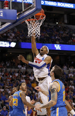 Florida Gators forward Alex Tyus scores over UCLA Bruins forward Reeves Nelson and UCLA Bruins' Tyler Honeycutt in the second half during their third round NCAA basketball game in Tampa